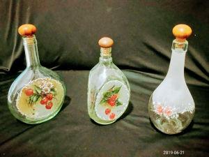 Lote com três garrafas de vidro translucido, duas com tampas em madeira, com rica policromia com jateamento,  e desenhos florais. Medindo : 28 cm a maior.