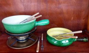 Aparelho de fondue em metal para queijo composto de  2 panelas de cerâmica na cor verde sendo a maior medindo 8X22 cm e a menor 0,7X19 cm acompanha 6 garfos de metal com cabos de madeira. (urigem suiça