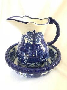 Jarro e bacia em porcelana, ambos decorados com paisagem na tonalidade azul. Med. bacia: 35 cm de diam. jarro: 28x30 cm.