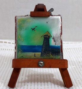 Decorativo tripé de pintor com pequena tela de óleo sobre espelho medindo 11,5 X 8,5 cm.