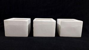 Lote contendo 3 cachepots em cerâmica vitrificada de tom branco no formato de bloco quadrado. Medem 8,5 X 11 X 11 cm cada.
