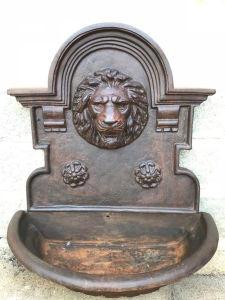 Fonte de parede em ferro, ornada com a face de um leão. Med. 80x45x95 cm.