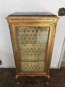 Vitrine estilo Luís XV, encimada com mármore, com fundo em forração capitonê na cor dourada, duas prateleiras internas em vidro e base interna em espelho. Med. 0,62x0,43x1,34 m.