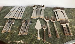 Faqueiro em inox com detalhes em dourado, contendo 76 peças, sendo: 12 facas, 12 garfos, 12 colheres, 12 garfos de sobremesa, 12 colheres de chá, 12 colheres de café, 2 colheres para servir, 1 colher para açucareiro e 1 espátula.