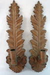 Par de apliques de parede no estilo barroco, em madeira nobre entalhada no formato de folhagem para uma vela cada, com resquícios de policromia em dourado. Med. 50 x 15 x 9 cm cada