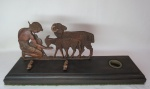 Antigo tinteiro de coleção em bronze representando Pastor com rebanho de ovelhas. Base em jacarandá com suporte duplo para canetas, recipiente para tinta em baquelite. Med. 11,5 x 35 x 9,5 cm.