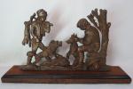 Antiga escultura de origem Européia em bronze, representando caçador carregando sua caça lebre e veado e seu cão ao lado. Possui base de madeira nobre. Med. 23,5 x 43 x 8 cm.